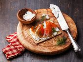 Sandwich On Crisp Bread With Smoked Salmon And Soft Cream Cheese On Olive Wood Plate