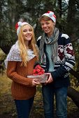 Young couple in love wearing Santa hats, holding a gift. Man and woman celebrating Christmas and New