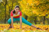 Young brunette woman doing yoga exercises in a autumn park.