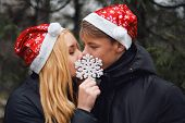 Happy young couple in love wearing Santa hats kissing and holding a big snowflake. Man and woman cel