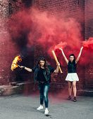 foto of teen smoking  - Two Bad girls with Molotov cocktail and red smoke bomb in the street - JPG