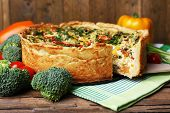 Vegetable pie with broccoli, peas, tomatoes and cheese on napkin, on wooden background