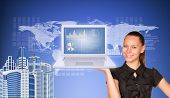 Beautiful businesswoman in dress smiling and holding latop with graphs. Buildings, world map, text r