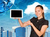 Beautiful businesswoman holding hand tablet with blank screen. Buildings, money and Earth as backdro