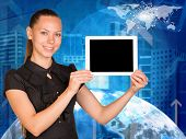 Beautiful businesswoman holding tablet pc with blank screen. Buildings and Earth as backdrop