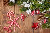 Christmas wooden background with snow fir tree, candy canes and decor