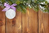 Christmas fir tree and bauble with purple ribbon on rustic wooden board with copy space