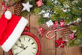 Christmas wooden background with snow fir tree, decor and clock with santa hat. View from above