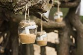 Beautiful decorated romantic place for a date with jars full of candles hunging on tree. Copy Space