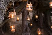Beautiful decorated romantic place for a date with jars full of candles hunging on tree and standing