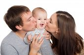 Happy young parents hug and kiss a beloved son