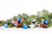 Christmas fir tree branch with holly berry and decor over snow