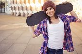 Brunette teenage girl in hipster outfit (jeans shorts keds plaid shirt hat) with a skateboard at the