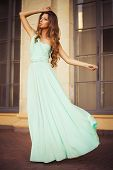 Beautiful blonde with a long curly hair in a long evening dress in motion outdoors near retro vintag