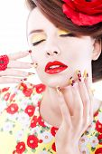 Brunette woman in yellow and red dress with poppy flower in her hair, poppy ring and creative nails,