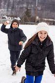 boy throw snow ball to the running girl