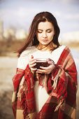 Brunette woman near lake in autumn in plaid drinking tea. outdoors, winded weather