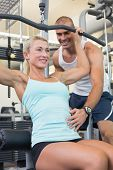 Male trainer assisting beautiful young woman on a lat machine in gym