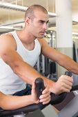 Determined handsome young man working out on exercise bike at the gym