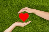 Two Woman's hands holding red heart