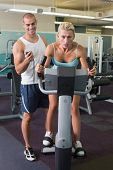 Smiling male trainer timing his client on exercise bike at the gym