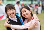 picture of degree  - Thai girl is hugging her friend who graduated a master degree - JPG