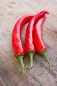 stock photo of red hot chilli peppers  - Hot red chili or chilli peppers over wooden background - JPG