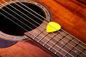 image of guitar  - Vintage acoustic guitar and guitar pick resting on the strings - JPG