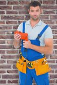 stock photo of overalls  - Confident male carpenter in overall holding drill machine against red brick wall - JPG