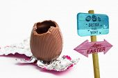 image of easter candy  - Easter egg hunt sign against easter egg unwrapped in pink foil with bite taken out - JPG