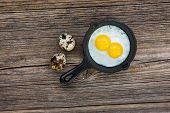 stock photo of quail  - Fried quail eggs in pan on wooden background - JPG