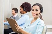 pic of clipboard  - Portrait of smiling female customer service representative writing on clipboard with colleagues working in background at call center - JPG
