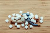 foto of obese  - Drop Dead doll man under falling sugar cubes for the concept of high blood sugar obesity diabetic - JPG
