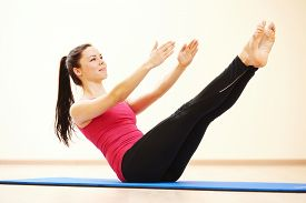 stock photo of pilates  - young female instructor doing stretching pilates exercises in sport club - JPG