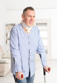 stock photo of crutch  - Standing man with crutches and cervical collar - JPG