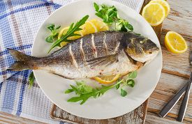 picture of sea fish  - Fried sea bream fish on plate with fresh salad and lemon - JPG