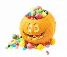 stock photo of jack-o-laterns-jack-o-latern  - Jack o lantern Halloween pumpkin with the smiling face and filled with multiple colorful sweets and candies - JPG