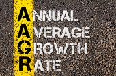 stock photo of average looking  - Concept image of Business Acronym AAGR as Annual Average Growth Rate written over road marking yellow paint line - JPG