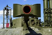 stock photo of artillery  - Cannon barrel of modern powerful green tank with rocket launcher and blue sky on background - JPG