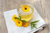 pic of linden-tree  - Linden honey in jar and calendula blossoms on wooden table - JPG