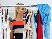 foto of antidepressant  - Thoughtful beautiful blonde woman standing near wardrobe rack full of clothes and choosing dress - JPG