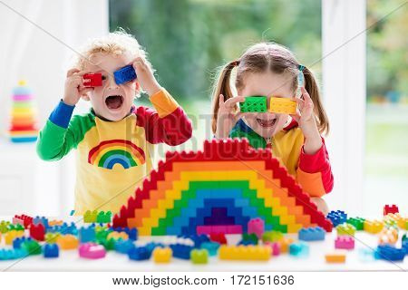 poster of Child playing with colorful toys. Little girl and funny curly baby boy with educational toy blocks. Children play at day care or preschool. Mess in kids room. Toddlers build a tower in kindergarten. Focus on girl.