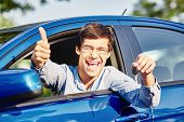 Close up of young happy hispanic man wearing glasses holding out car keys, showing thumb up hand ges poster