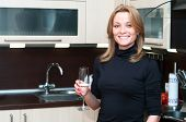 Beautiful Happy Smiling Woman In Kitchen Interior Drinking Champagne