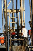 picture of roustabouts  - Roustabouts work on lower platform of oil drilling rig Kern County California - JPG