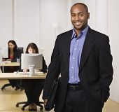 A young businessman is standing in an office with some other business people.  He is smiling at the