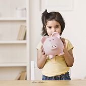 foto of indian money  - A young girl holding a pink piggy bank - JPG