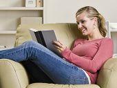 stock photo of girl reading book  - Teenage girl reading book in chair - JPG