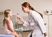 Doctor giving girl lollipop in doctor office