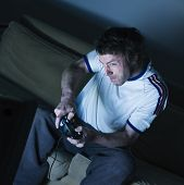 pic of video game  - pictures in a living room a funny and expresive man sitting on a couch playing video game - JPG